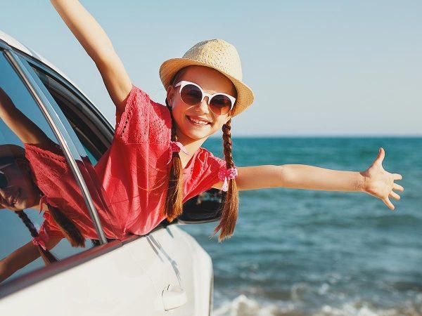 bambina sorridente trecce occhiali da sole si sporge finestrino auto mare