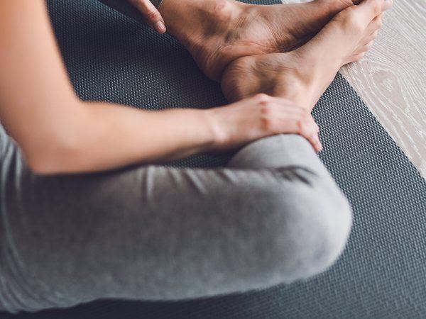 donna seduta a terra tappetino yoga piedi nudi leggins