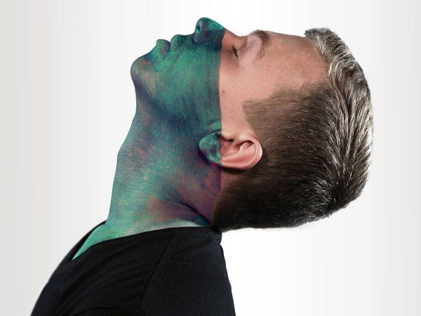 ragazzo biondo piega testa indietro maglietta nera mezzo viso colorato azzurro